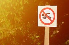 Eine Säule mit einem Zeichen, das ein Verbot auf Schwimmen bezeichnet Das Zeichen zeigt eine gekreuzte-heraus sich hin- und herbe Stockbilder