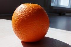 Eine saftige Orange auf dem Tisch, beleuchtet durch eine helle Morgensonne stockbilder