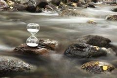 Eine Sanduhr auf einem Felsen eines Nebenflusses stockbild