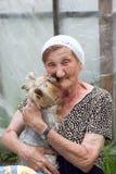 Eine schöne ältere Frau mit ihrem Hund in einem Sommergarten lizenzfreie stockbilder