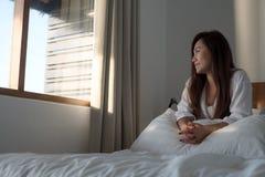 Eine schöne Asiatin, die auf dem Bett sitzt und außerhalb des Fensters schaut stockfotografie