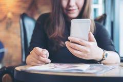 Eine schöne Asiatin mit smileygesichtsholding und -anwendung des intelligenten Telefons mit Zeitschriften Lizenzfreie Stockfotos
