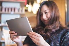 Eine schöne Asiatin mit smileygesichtsholding und die Anwendung von Tabletten-PC für machen ein Foto Stockfotografie
