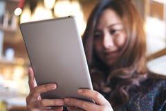 Eine schöne Asiatin mit smileygesichtsholding und die Anwendung von Tabletten-PC für machen ein Foto Stockbild