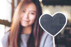Eine schöne asiatische Frau, die ein leeres Herzform-Tafelzeichen mit dem Fühlen glücklich hält lizenzfreies stockbild