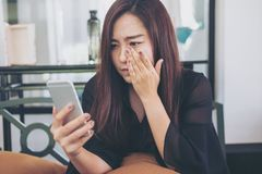 Eine schöne asiatische Frau, die intelligentes Telefon mit dem Fühlen traurig und Schrei betrachtet stockfotografie