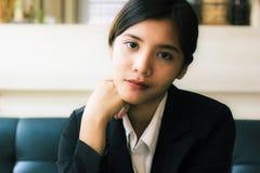 Eine schöne asiatische Geschäftsfrau, die auf Sofa sitzt und Kamera mit ihrem Lächeln schaut stockfoto
