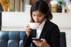 Eine schöne asiatische Geschäftsfrau, die auf Sofatrinkbecher heißem Kaffee sitzt und intelligentes Telefon verwendet lizenzfreie stockbilder