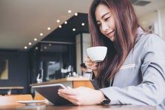Eine schöne asiatische Geschäftsfrau, die Tablette hält Stockbild
