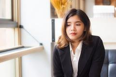 Eine schöne asiatische sitzende Entspannung der Geschäftsfrau auf Sofa und Denken etwas in der Kaffeestube lizenzfreies stockfoto