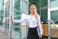 Eine schöne Bürodame, die eine Tür öffnet Lizenzfreie Stockfotografie