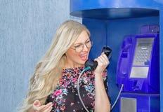 Eine schöne blonde Frau, die Gläser wiaring ist, hält einen Telefonhörer in einem Münztelefon Emotional Rufe in das Telefon stockfotos