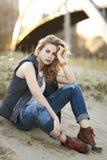Eine schöne blonde Frau, die im Sand in Chicago durch Michigansee sitzt Stockbilder
