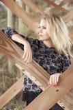Eine schöne blonde Frau, die unter einem Pier durch den Ozean weg schaut steht Stockfoto