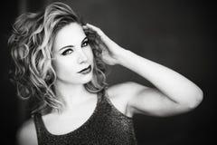 Eine schöne blonde Frau, die wie ein Modell mit ihrer Hand durch ihr Gesicht in Schwarzweiss aufwirft Lizenzfreie Stockbilder