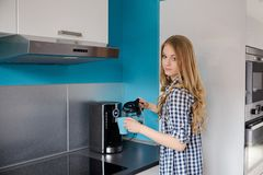 Eine schöne blonde Frau gießt Kaffee von der Kaffeemaschine in eine Schale Stockbilder