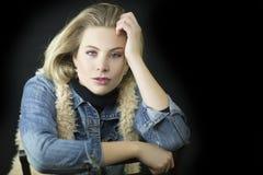 Eine schöne blonde Frau mit einer Baumwollstoffhemd- und -pelzweste und blaue Augen des Durchdringens in einem Studio Stockbilder