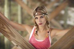 Eine schöne blonde Frau mit Zöpfen unter Pier in StAugustine, Florida Stockfotografie