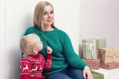 Eine schöne blonde Mutter, die ihren Sohn umarmt Stockbild