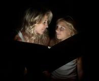 Eine schöne blonde Mutter und ihr Kind zusammen mit einem großen Buch in der Dunkelheit Stockbild
