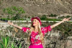 Eine schöne Blondine in einem Hut steht mit den Armen, die zum Himmel ausgestreckt werden Im Hintergrund gibt es einen Berg und e lizenzfreie stockfotos