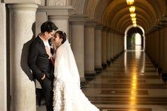 Eine schöne Braut und ein hübscher Bräutigam an der christlichen Kirche während der Hochzeit. Stockbilder