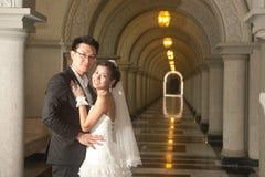 Eine schöne Braut und ein hübscher Bräutigam an der christlichen Kirche während der Hochzeit. Stockbild