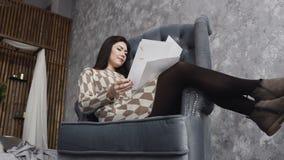 Eine schöne Brunettefrau sitzt auf einem weichen Lehnsessel in einem Kunststudio auf der grauen Wand des Hintergrundes und betrac stock footage