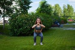 Eine schöne dünne Frauensportlerin, die Hocke tut lizenzfreies stockfoto