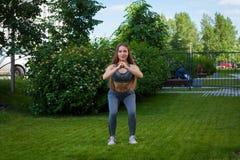 Eine schöne dünne Frauensportlerin, die Hocke tut lizenzfreies stockbild