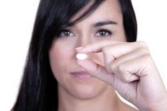 Eine schöne Frau, die eine Pille anhält Lizenzfreies Stockbild