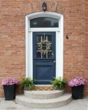 Eine schöne freundliche blaue Haustür mit einem willkommenen Kranz lizenzfreies stockbild