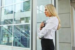 Eine schöne Geschäftsfrau, die aus Fenster mit Druck heraus schaut Stockbild