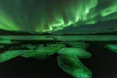 Eine schöne grüne und rote Aurora, die über das Jokulsarlon tanzt Stockfotografie
