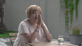 Eine schöne Greisin setzt beide Hände auf ihren Kopf Sie sitzt in der Terrasse mit einem Glas Wasser stock footage