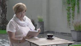 Eine schöne Greisin sitzt in der Terrasse draußen Sie nimmt ihre Gläser und fängt an zu lesen stock video