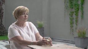 Eine schöne Greisin trinkt Wasser mit Zitrone Sie sitzt in der Terrasse stock video footage