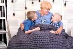 Eine schöne Großmutter und zwei Enkel sitzen auf dem Sofa unter einer gestrickten Merinowolledecke Eine glückliche Familie lizenzfreie stockfotografie