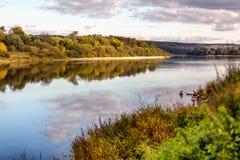Eine schöne Herbstlandschaft, ein Wald reflektierte sich in einem Fluss, lizenzfreies stockbild