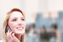 Eine schöne junge blonde Frau, die einen Telefonanruf mit Kopienraum macht Stockfotografie