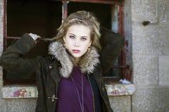 Eine schöne junge blonde Frau in einer städtischen Landschaft im Winter Lizenzfreies Stockfoto