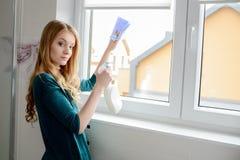 Eine schöne junge blonde Frau wäscht ein Fenster Stockfoto