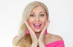 Eine schöne junge Blondine mit einem überraschten Lächeln und dem Halten ihrer Hände vor ihrem Gesicht, ihren Mund öffnend lizenzfreie stockfotografie