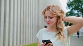 Eine schöne junge Dame, die draußen einen Handy verwendet Stockfoto