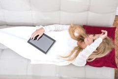 Eine schöne junge Frau auf dem Sofa Lizenzfreie Stockfotos