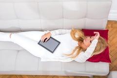 Eine schöne junge Frau auf dem Sofa Stockfotografie