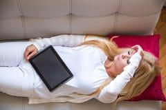 Eine schöne junge Frau auf dem Sofa Lizenzfreie Stockfotografie