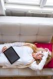 Eine schöne junge Frau auf dem Sofa Lizenzfreies Stockbild