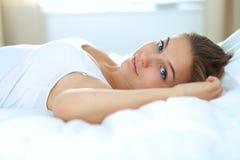 Eine schöne junge Frau bequem und, die himmlisch im Bett liegt lizenzfreies stockfoto
