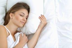 Eine schöne junge Frau bequem und, die himmlisch im Bett liegt lizenzfreie stockfotos